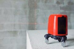 Аппаратура уровня лазера на кирпиче на рабочем месте конструкции Стоковая Фотография