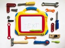 Аппаратуры игрушки детей вокруг доски для текста Стоковая Фотография