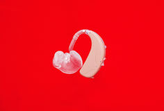 Аппарат для тугоухих на красном цвете Стоковое Фото