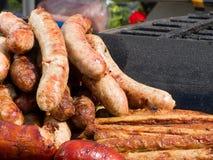 Аппетитная очень вкусная зажаренная сосиска frankfurters мяса на барбекю жарит outdoors Стоковые Изображения RF