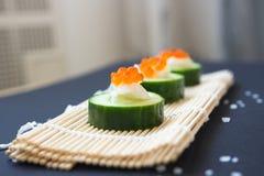 аппетитно Огурец с плавленым сыром икры и на бамбуковой циновке стоковое фото rf