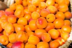 Аппетитные абрикосы в плетеных корзинах на счетчике в рынке стоковое фото