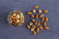 Аппетитные гайки грецких орехов, миндалин и фундуков в стеклянной вазе на серой предпосылке ткани для здоровой закуски Стоковые Изображения RF