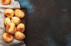 Аппетитные домодельные смачные плюшки сыра на коричневой предпосылке кухонного стола, взгляде сверху E стоковое изображение