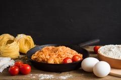 Аппетитные традиционные классические итальянские макаронные изделия с томатным соусом и базилик в черной сковороде на деревянном  стоковые изображения rf