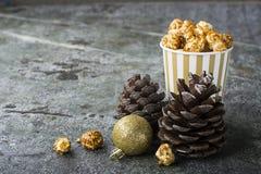 Аппетитный золотой попкорн карамельки в бумаге striped чашки в интерьере с конусами ели, ` s ` s Нового Года Нового Года золотом Стоковое Изображение