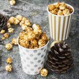 Аппетитный золотой попкорн карамельки в бумаге striped чашки в интерьере с конусами ели, ` s ` s Нового Года Нового Года золотом Стоковое Фото