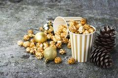 Аппетитный золотой попкорн карамельки в бумаге striped чашки в интерьере с конусами ели, ` s ` s Нового Года Нового Года золотом Стоковое Изображение RF