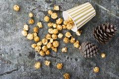 Аппетитный золотой попкорн карамельки в бумаге striped чашки в интерьере с конусами ели, ` s ` s Нового Года Нового Года золотом Стоковые Фото