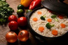 Аппетитный здоровый рис с овощами в белой плите на древесине Стоковая Фотография