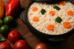 Аппетитный здоровый рис с овощами в белой плите на древесине Стоковое Изображение