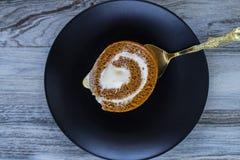 Аппетитный крен теста тыквы с сливк взбитой сливк на плите на винтажной деревянной предпосылке Стоковое Фото