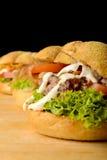 3 аппетитных бургера на деревянном столе Стоковая Фотография