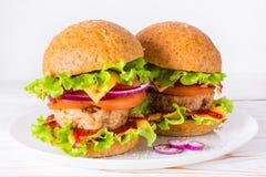 2 аппетитных гамбургера на плите на таблице Стоковая Фотография RF