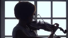 Аппликатура девушки строки играя на скрипке против окна силуэт сток-видео