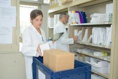 Аптекарь держа цифровой планшет в stockroom фармации стоковые фото
