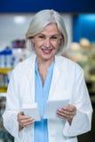 Аптекарь держа медицину и рецепт в фармации Стоковая Фотография