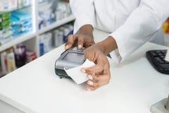 Аптекарь держа получение пока кнопка ` s читателя отжимая карточки стоковое фото