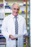 Аптекарь держа рецепт и медицину Стоковая Фотография