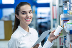 Аптекарь держа рецепт пока проверяющ медицину в фармации Стоковое Изображение