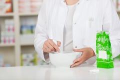 Аптекарь задавливая медицину в миномете на счетчике фармации Стоковые Изображения