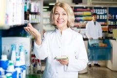 Аптекарь и техник фармации представляя в аптеке Стоковое Изображение