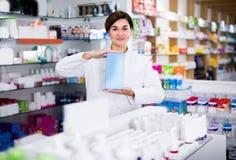 Аптекарь маленькой девочки показывает правое лекарство стоковая фотография