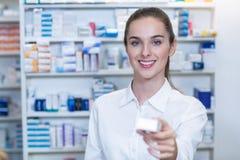 Аптекарь показывая медицину в фармации Стоковые Изображения