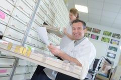 Аптекарь портрета положительный дружелюбный работая в современном farmacy Стоковое Фото