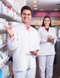 Аптекарь представляя в аптеке Стоковые Изображения