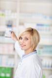 Аптекарь принимая вне медицину от полки в фармации Стоковое Фото