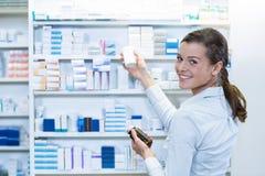 Аптекарь проверяя медицину в полке на фармации Стоковые Изображения