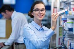 Аптекарь проверяя медицину в фармации Стоковые Фото