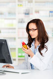 Аптекарь работая на ее компьютере Стоковые Фото