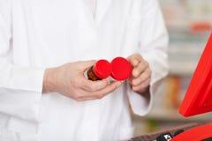 Аптекарь сравнивая бутылки Стоковые Изображения RF
