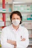 Аптекарь с маской пересеченной оружиями нося в фармации Стоковое Изображение RF