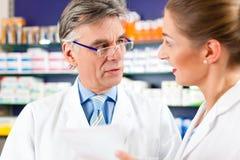 2 аптекаря в советовать с фармации Стоковое фото RF