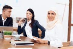Арабская женщина в hijab работает в офисе вместе с ее коллегами стоковое изображение rf