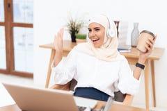 Арабская женщина в hijab слушает к музыке на наушниках стоковое фото rf
