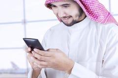 Арабская персона с мобильным телефоном в зале авиапорта Стоковая Фотография RF