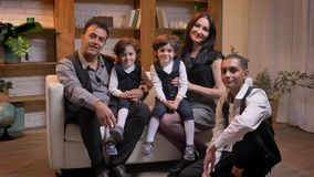 Арабская семья сидя на софе и наблюдая в камеру с улыбкой в живя комнате видеоматериал