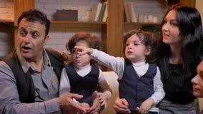 Арабская семья сидя на софе и разговаривая с seach другое в живущей комнате видеоматериал
