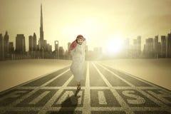 Арабские бега бизнесмена через финишную черту Стоковые Фото