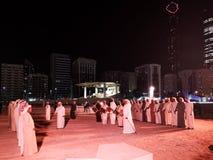 Арабские ближневосточные люди выполняя традиционный танец в Абу-Даби, ОАЭ вечером стоковое изображение