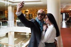 Арабский бизнесмен и девушка делая selfie стоковая фотография rf