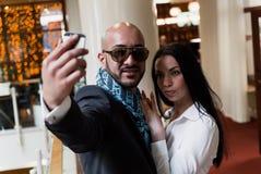 Арабский бизнесмен и девушка делая selfie стоковая фотография