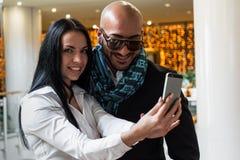 Арабский бизнесмен и девушка делая selfie стоковые изображения rf