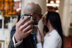 Арабский бизнесмен и девушка делая selfie стоковое фото