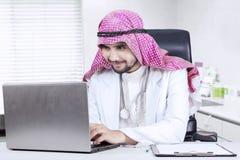 Арабский доктор используя компьтер-книжку на столе Стоковые Фотографии RF