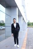 Арабский парень в деловом центре стоит усмехаясь идти медленный Стоковые Изображения RF